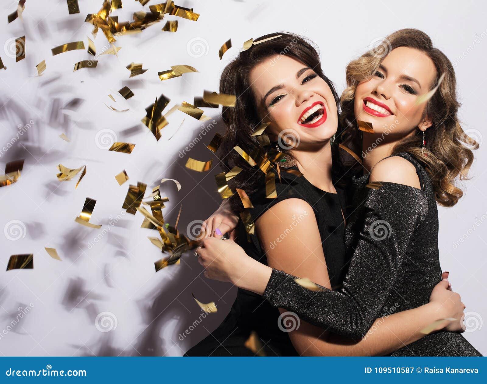 Pares de dos Rich Women Laughing con el cristal de Champán lujo Party el tiempo