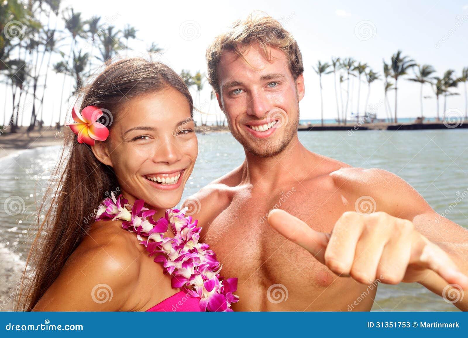 Pares de Hawaii felices en la playa hawaiana
