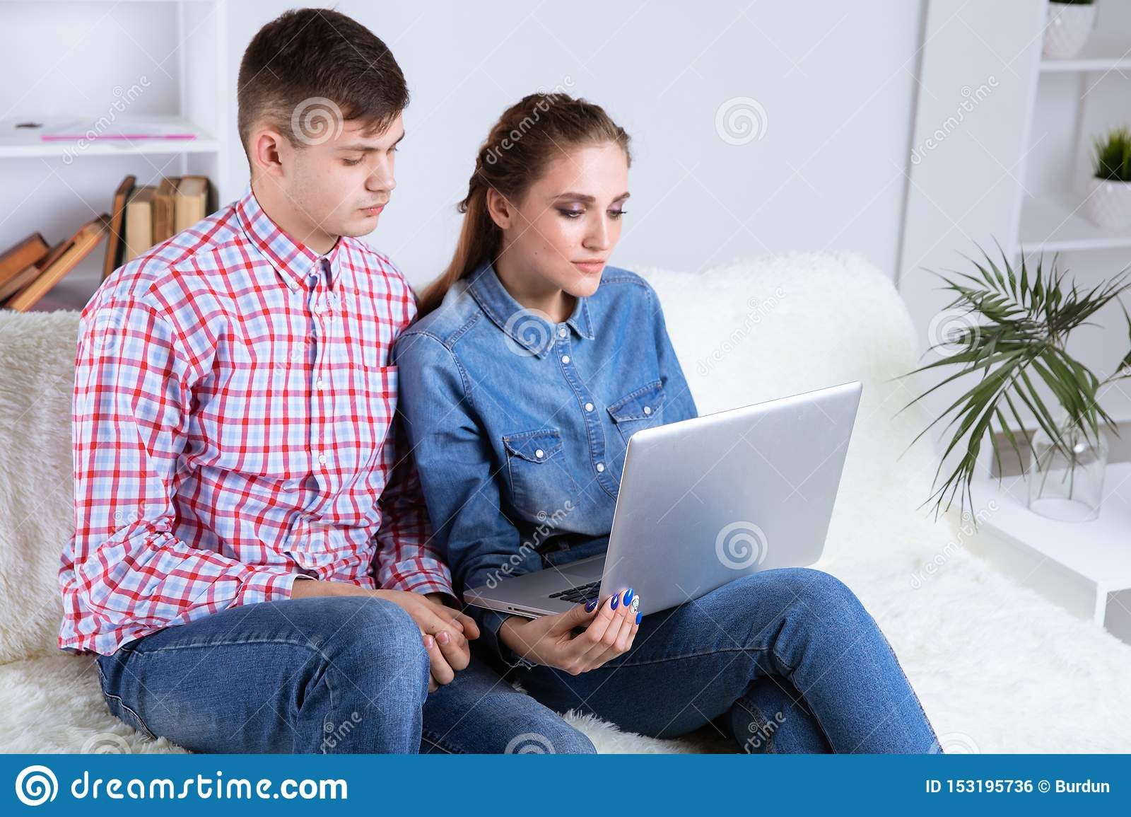 Pares de homem novo e de mulher em linha no Internet que senta-se em um sofá em casa