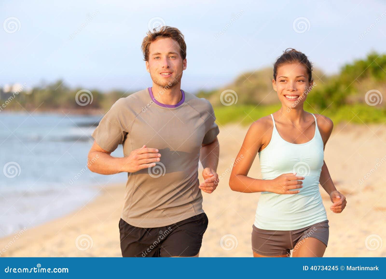 Pares de la aptitud que activan afuera en la sonrisa de la playa