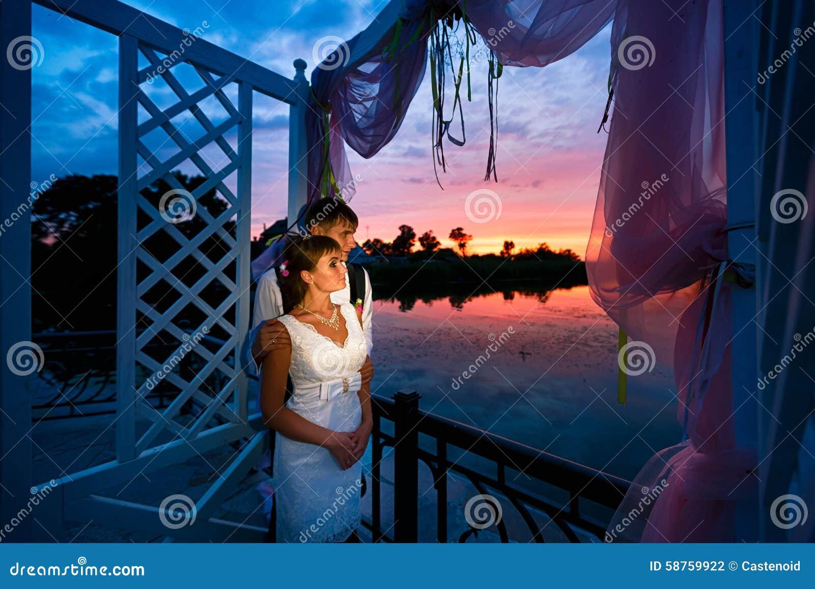 Pares de la boda en amor en el tiempo de la puesta del sol