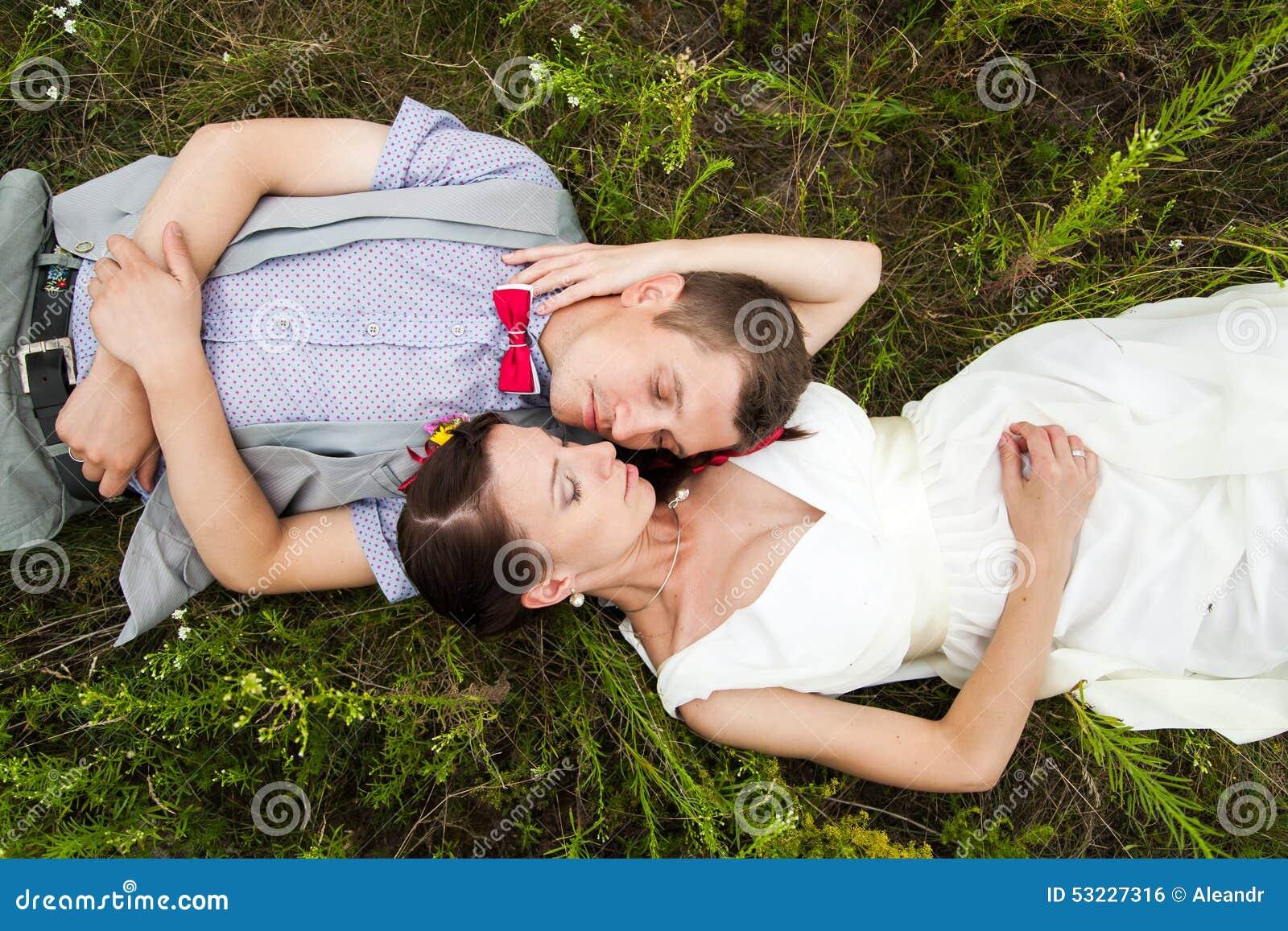 Pares de la boda en el amor que miente en hierba verde en prado del verano