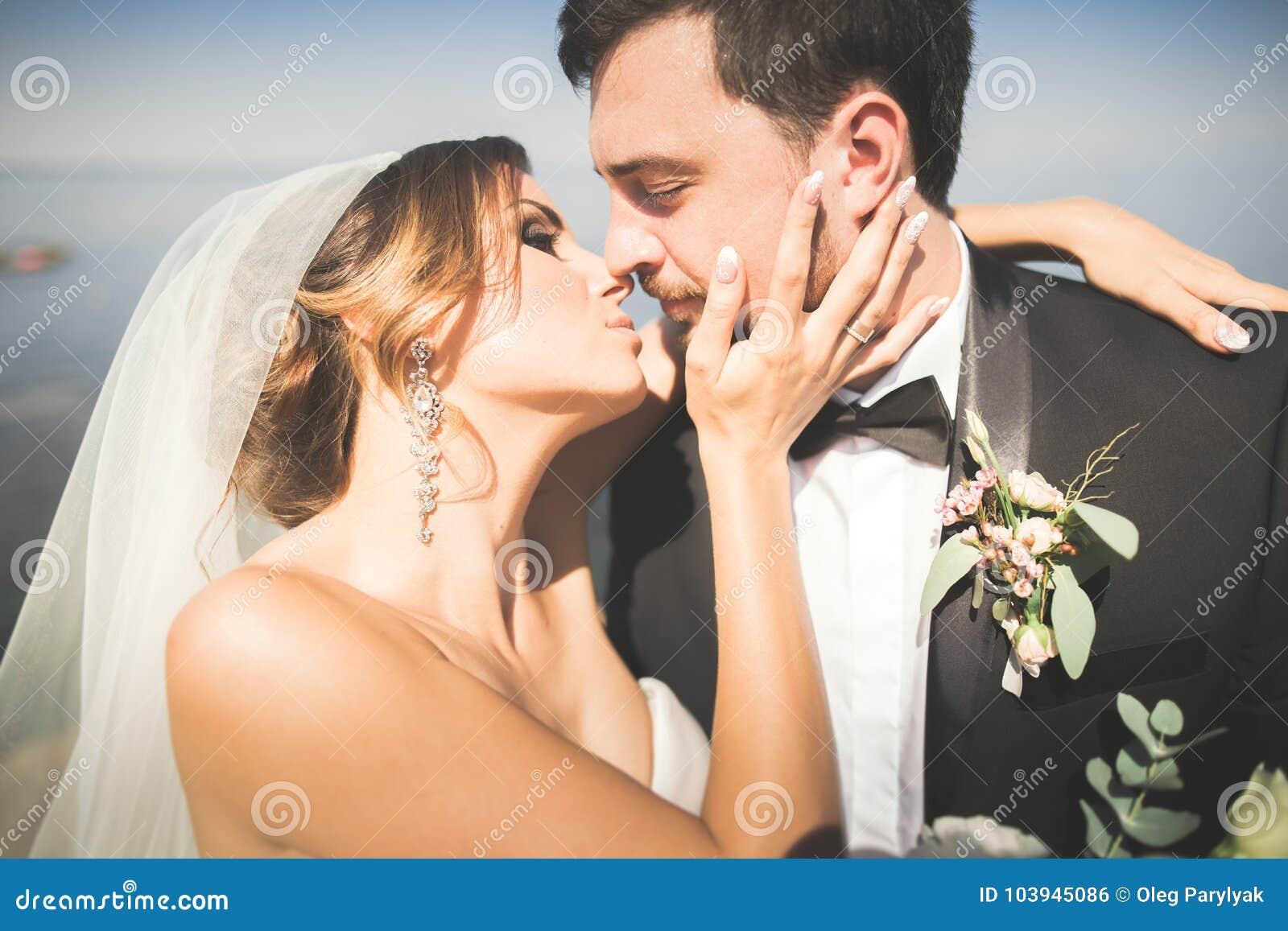 Pares de la boda, novio, novia con el ramo que presenta cerca del mar y cielo azul