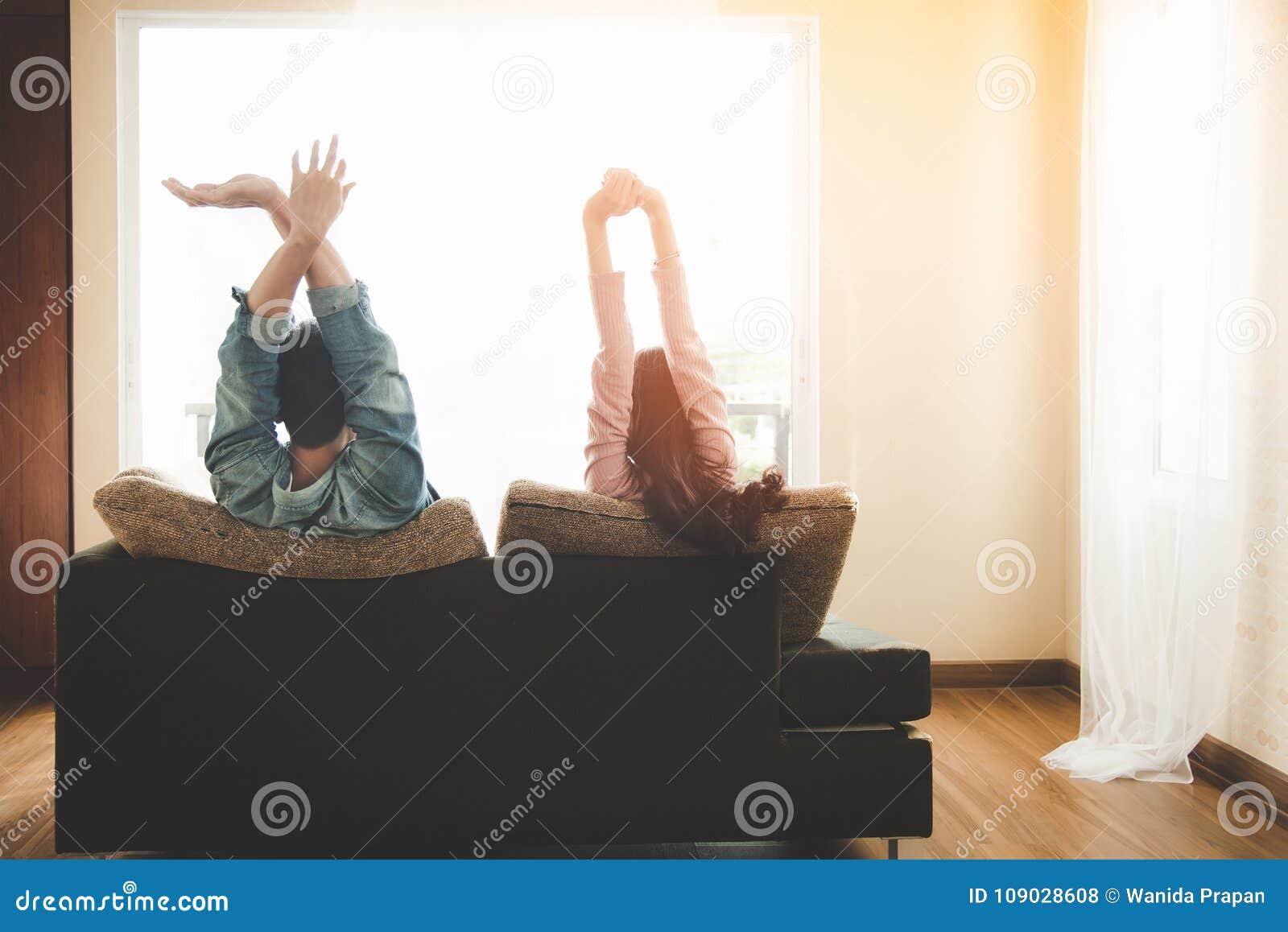 Pares de la forma de vida en amor y relajación en un sofá en casa y mirada afuera a través de la ventana de la sala de estar
