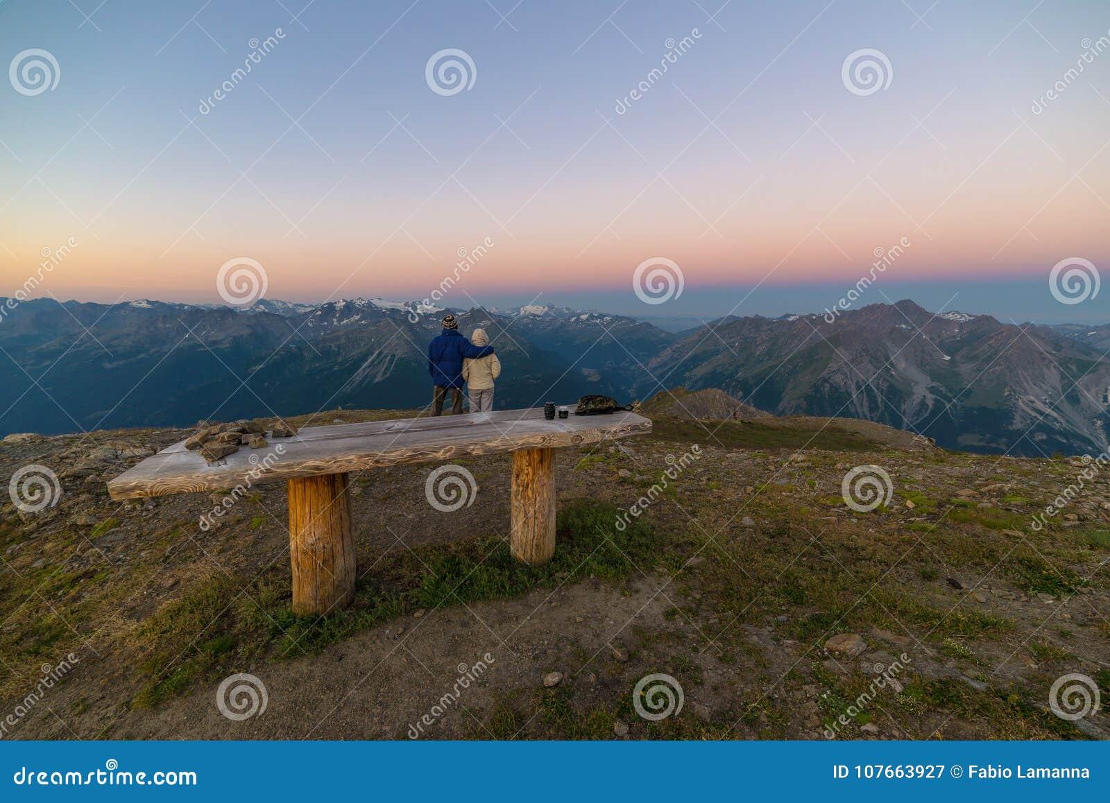 Pares de la gente que mira la salida del sol sobre pico de montaña de Mont Blanc 4810 m ` Aosta de Valle d, aventuras italianas d