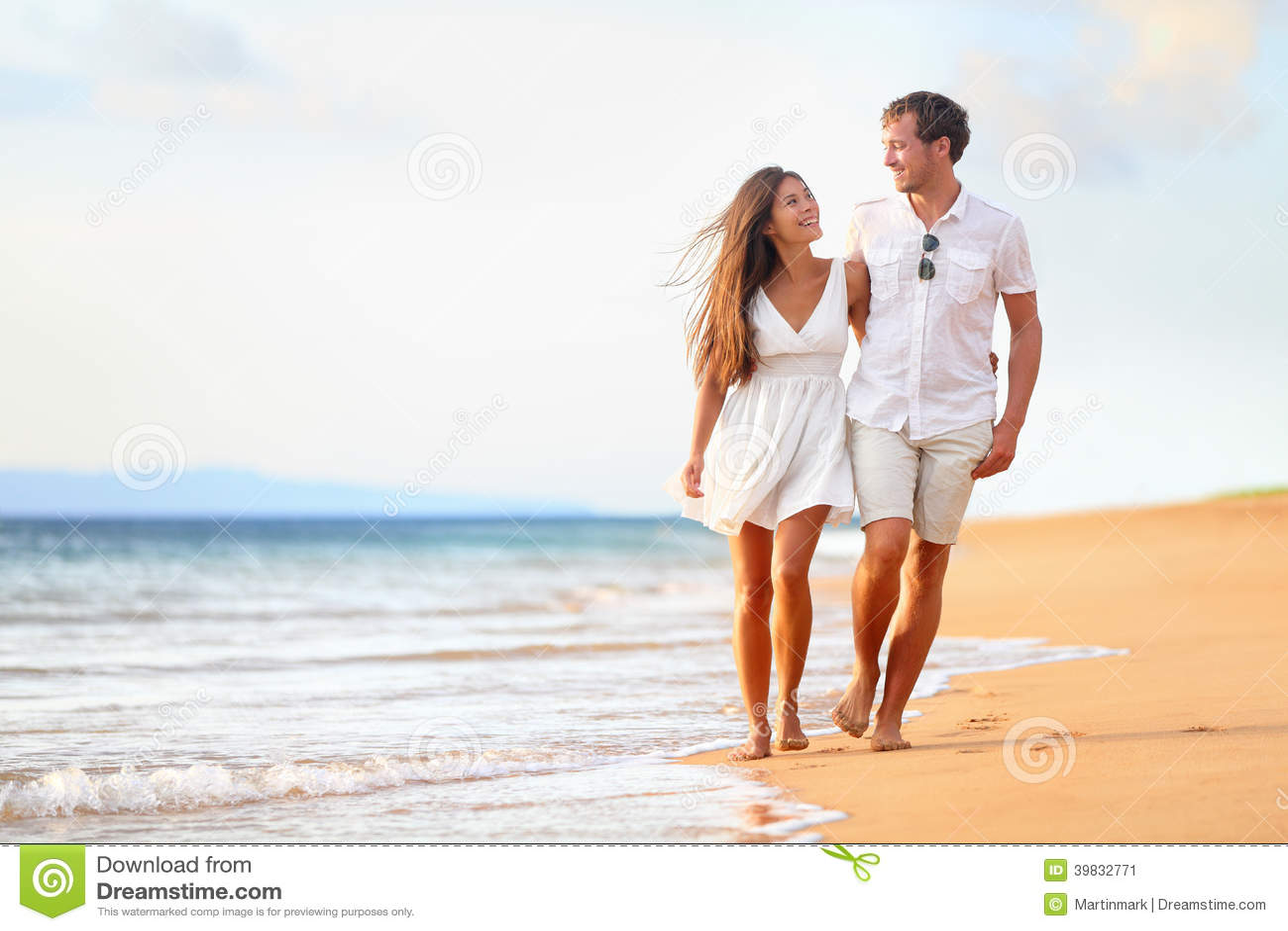 Pares de la playa que caminan en viaje romántico