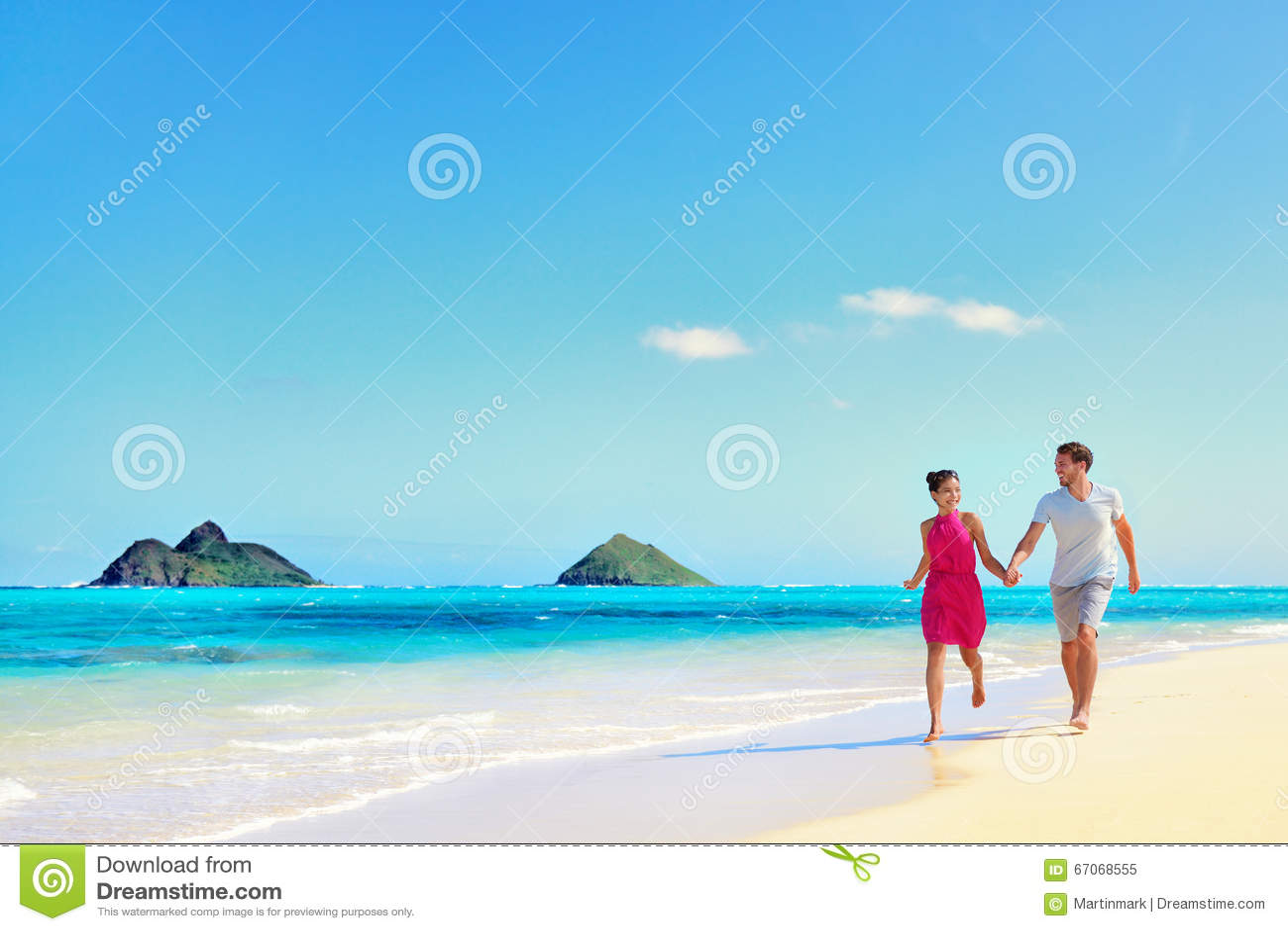 Pares de las vacaciones de Hawaii que caminan en la playa de la turquesa