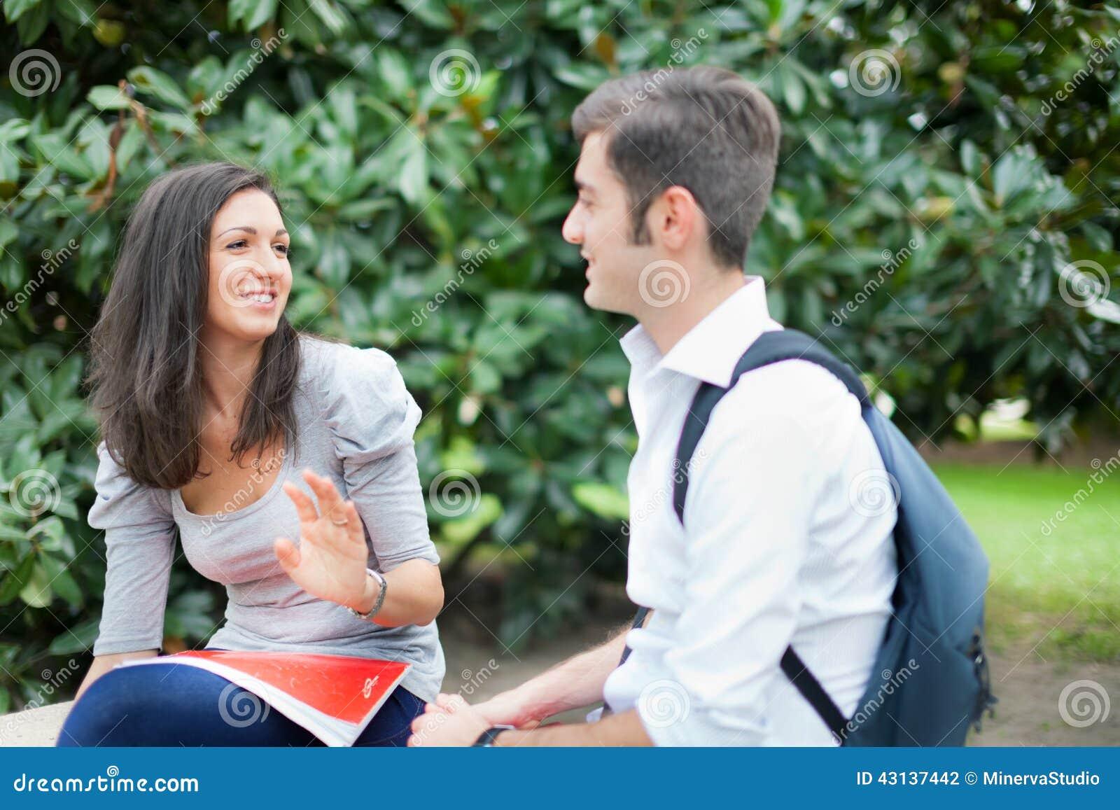 Pares de los estudiantes que hablan al aire libre