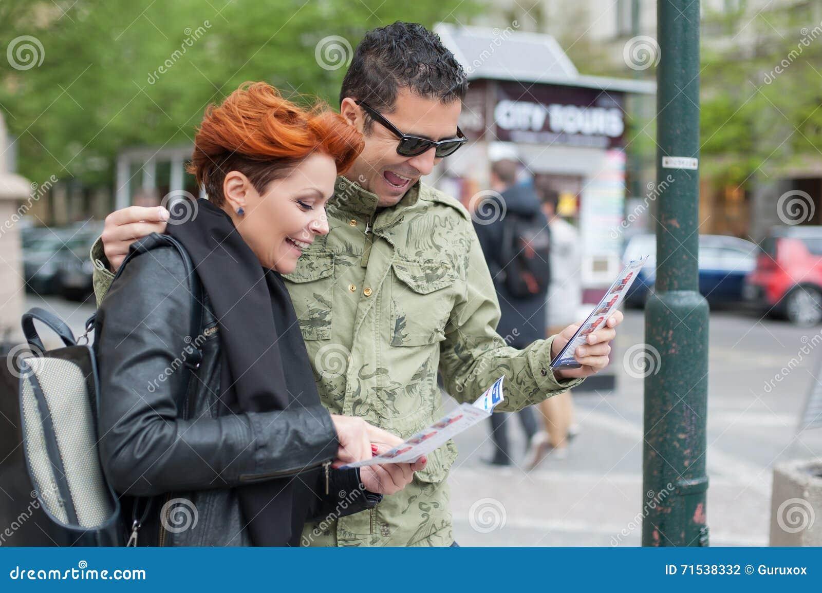 Pares de los turistas que miran la guía de la ciudad