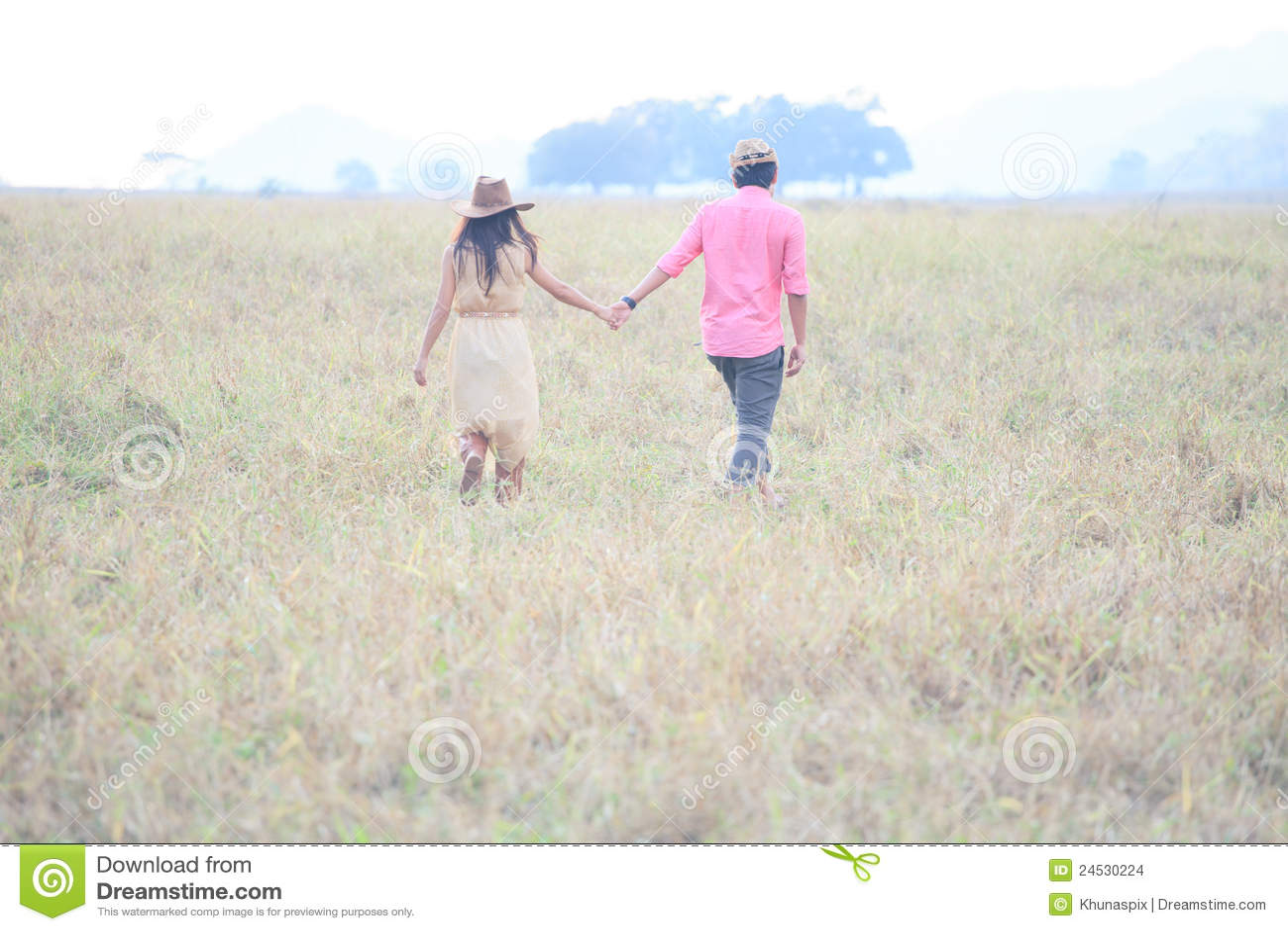 Pares de mão da terra arrendada do homem e da mulher no campo de grama