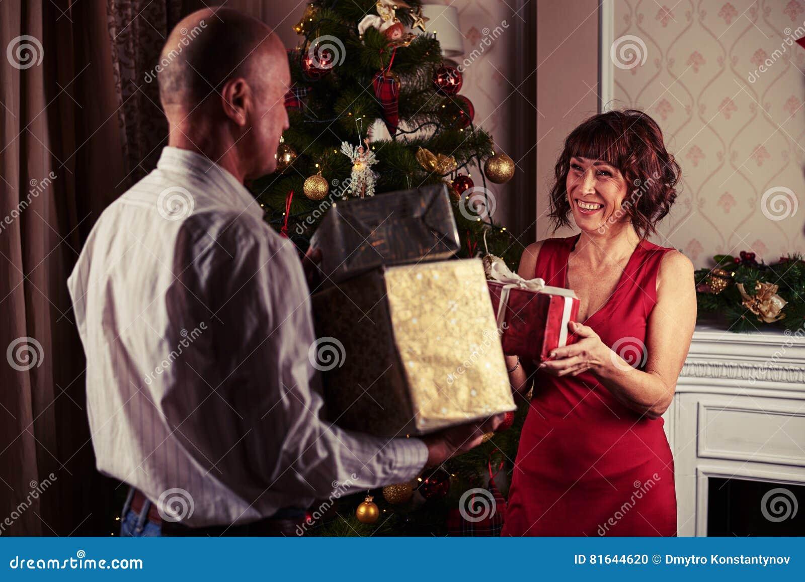 Pares de mediana edad que intercambian los regalos mientras que se coloca cerca de Christma