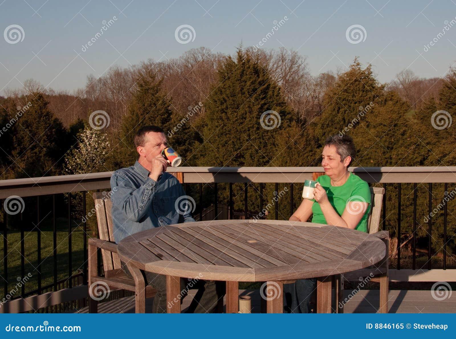 Pares de meia idade que relaxam na plataforma