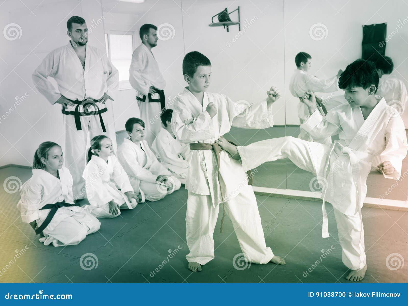 Pares de meninos que praticam movimentos novos do karaté