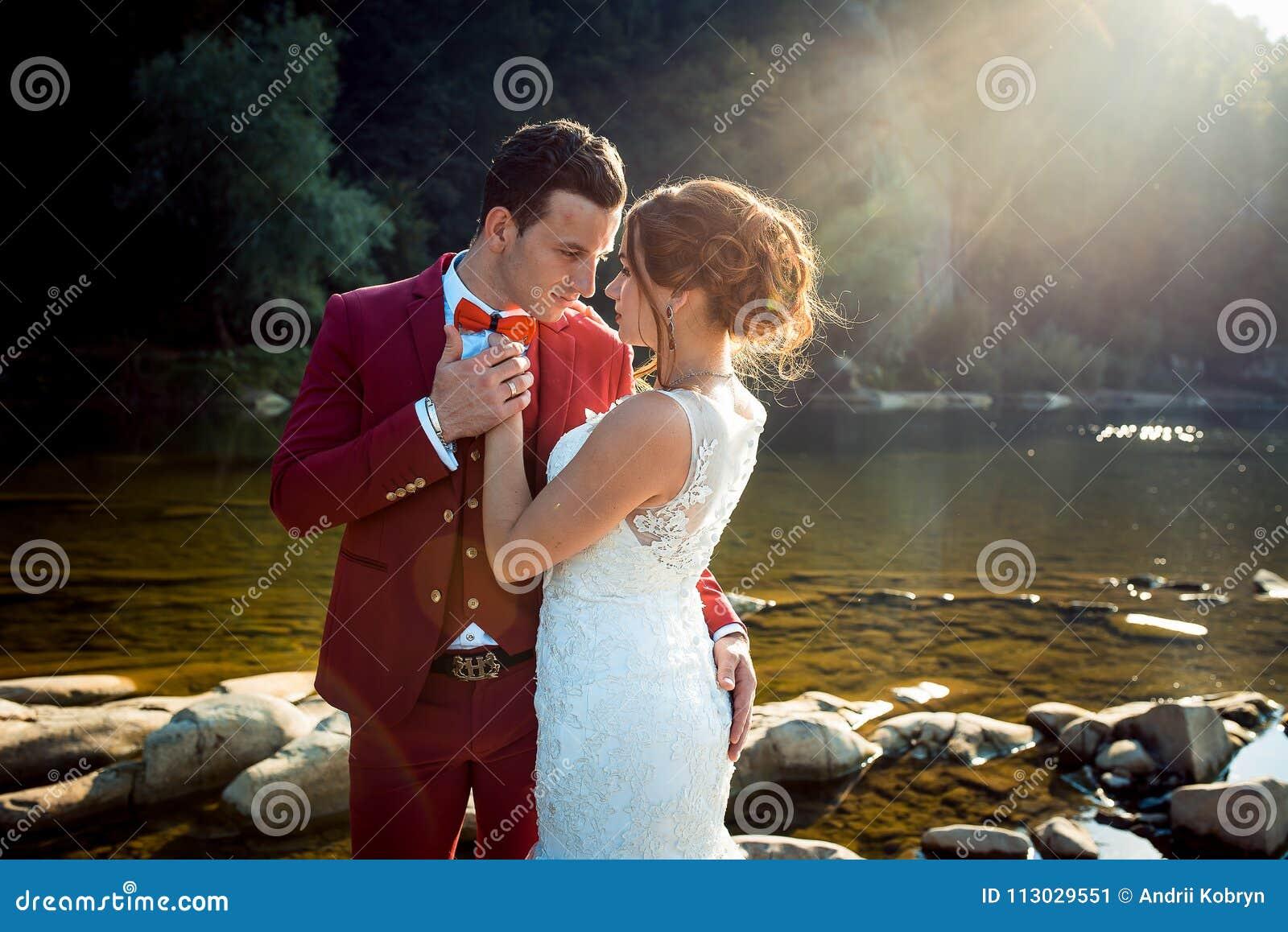 Pares de moda encantadores del recién casado del medio retrato de la longitud que abrazan la puesta del sol del río del paisaje d