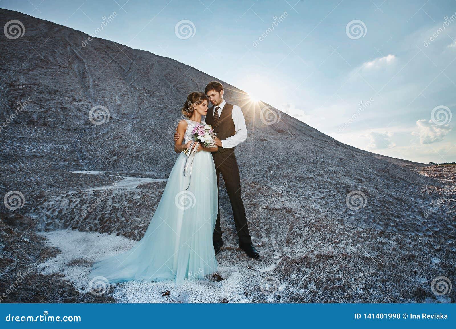 Pares de moda y hermosos, muchacha modelo rubia feliz con el peinado elegante, en un vestido blanco del cordón y elegante