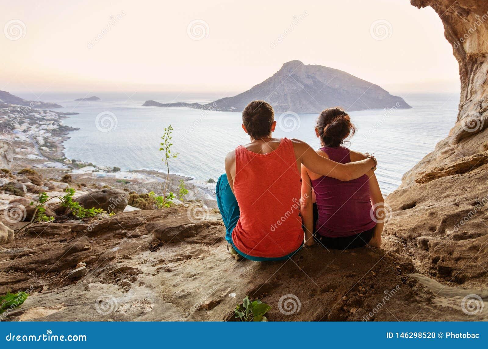 Pares de montanhistas de rocha que têm o resto ao sentar-se no fundo do penhasco e ao apreciar a vista pitoresca da ilha de Telen