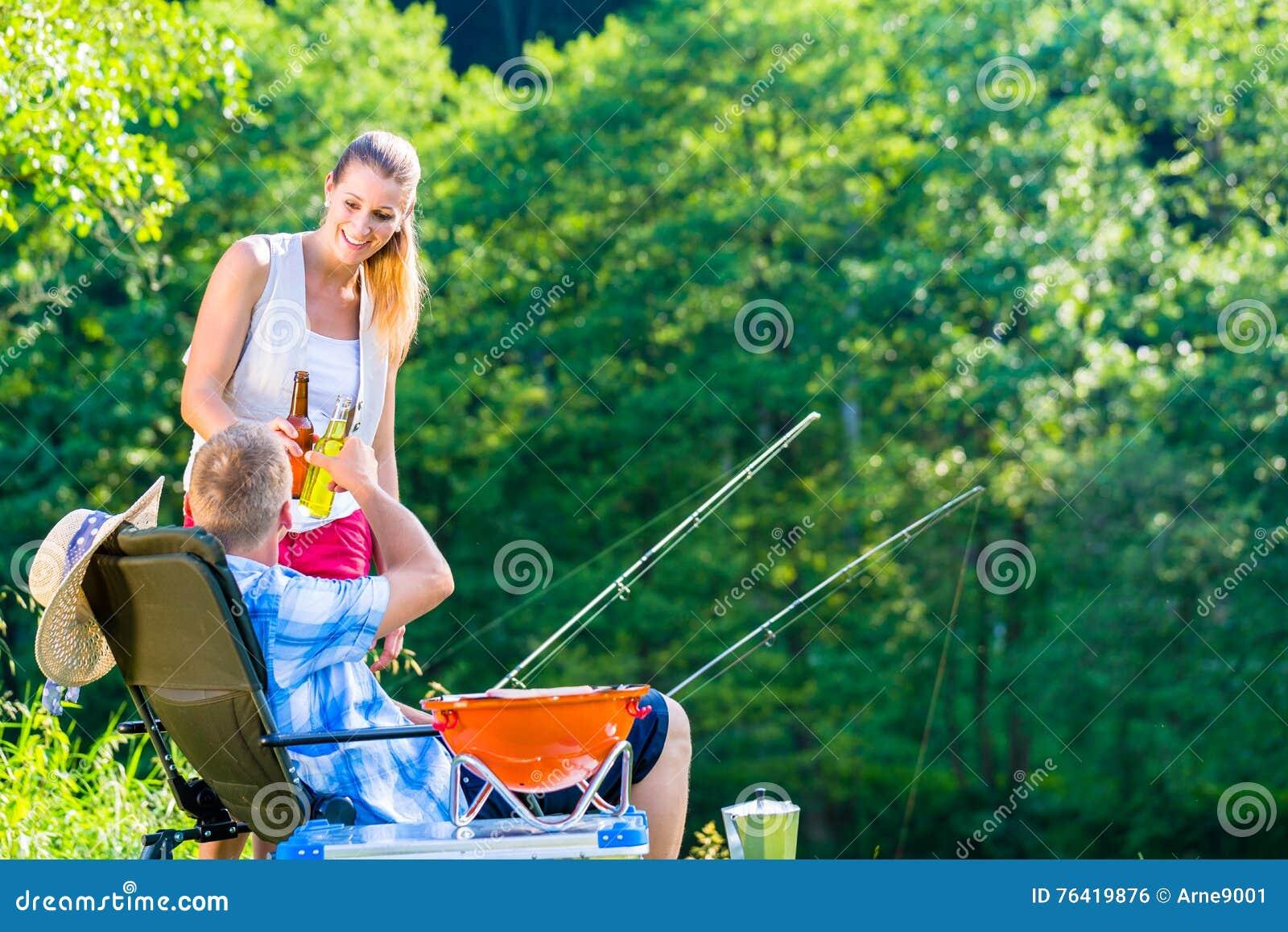 Pares de mulher e de homem que comem a cerveja quando pesca desportiva