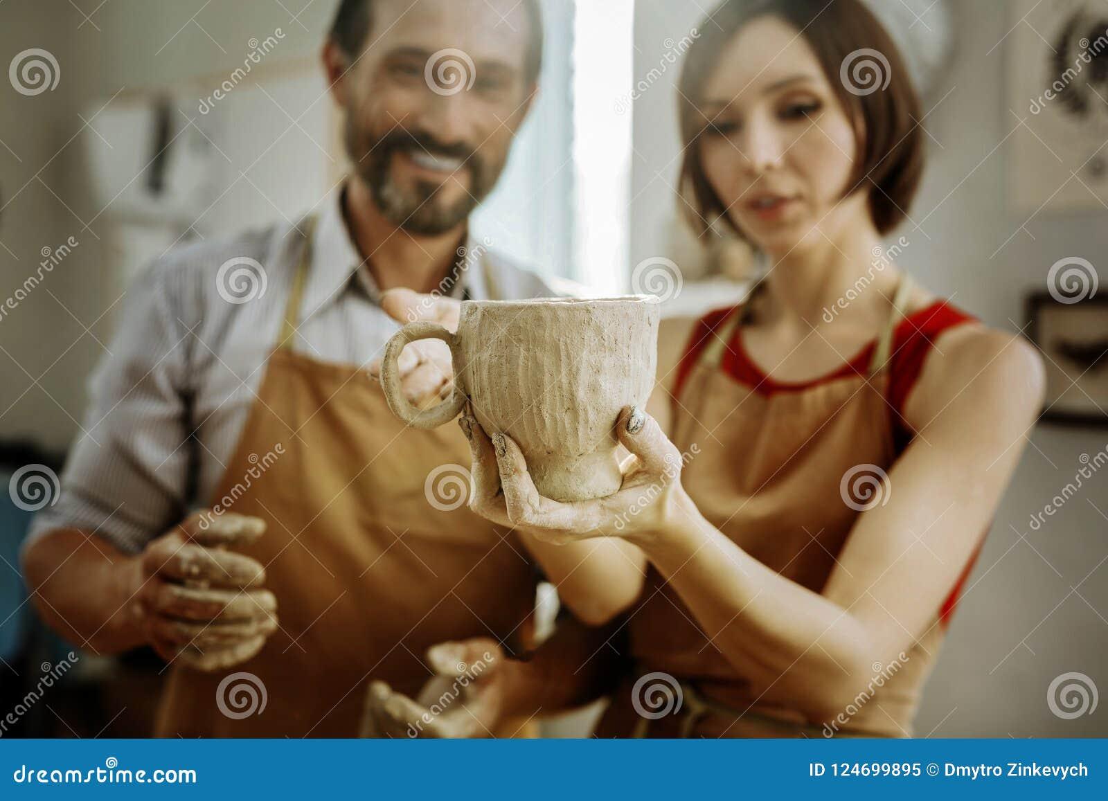 Pares de oleiro que sentem felizes após ter feito o copo grande agradável