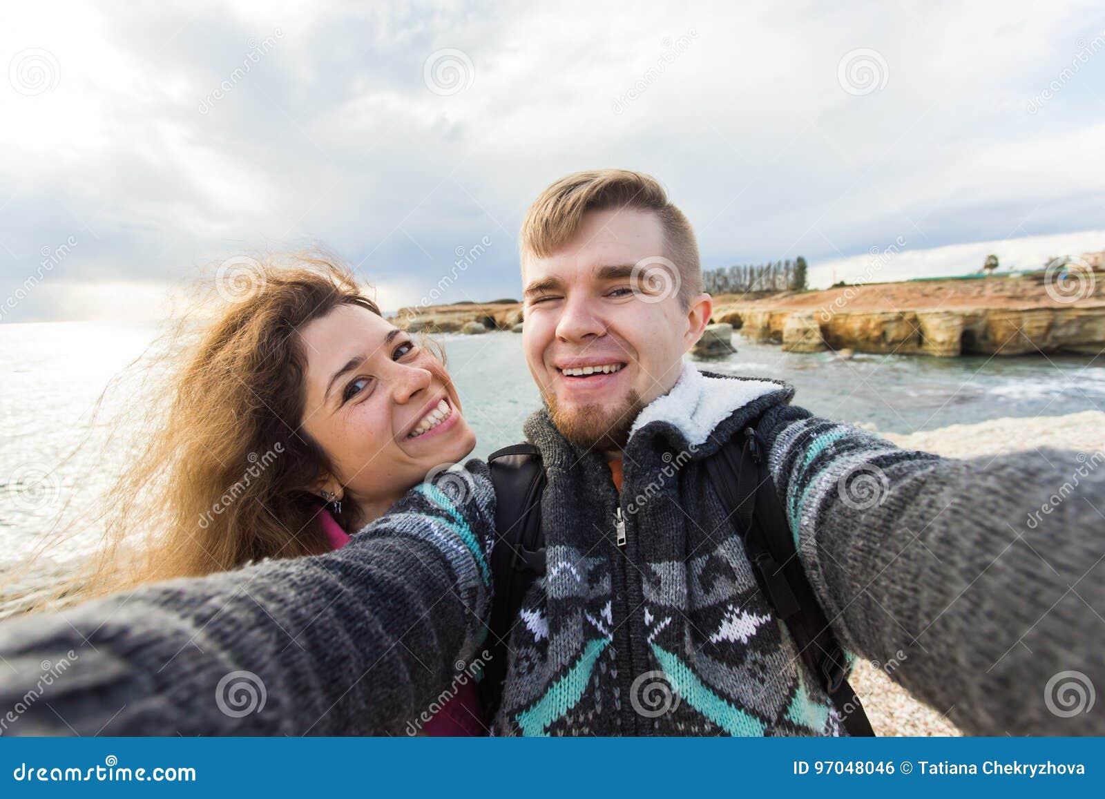Pares de risa jovenes que caminan tomando el selfie con el teléfono elegante Hombre joven feliz y mujer que toman el autorretrato