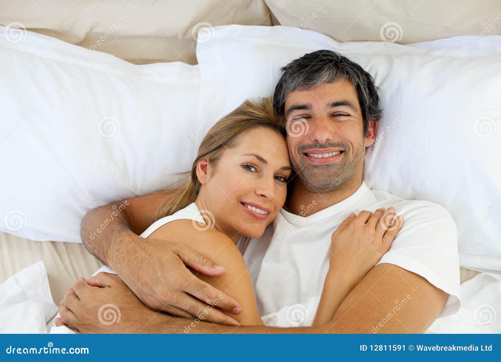 Pares de sorriso que abraçam o encontro na cama