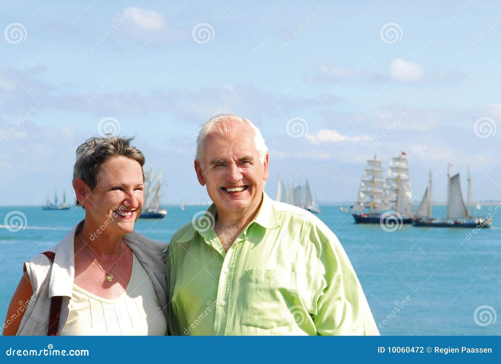 Pares de sorriso sênior com oceano cénico