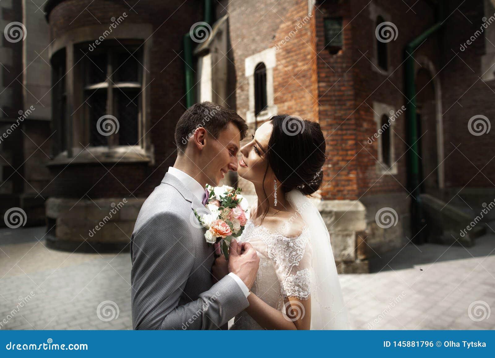 Pares de sorriso de surpresa do casamento Noiva bonita e noivo à moda perto da igreja