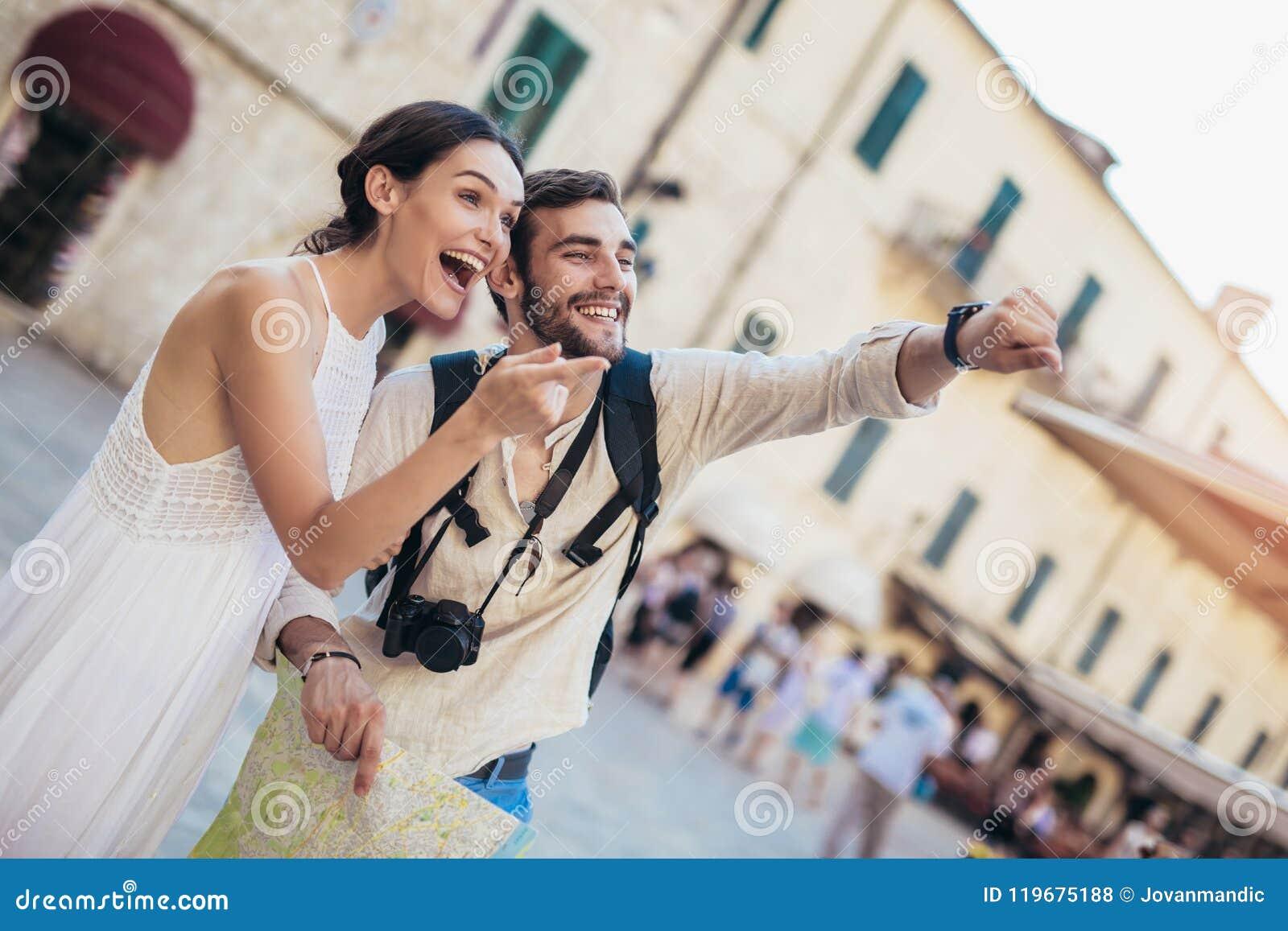 Pares de sorriso de turistas nos óculos de sol com o mapa na cidade