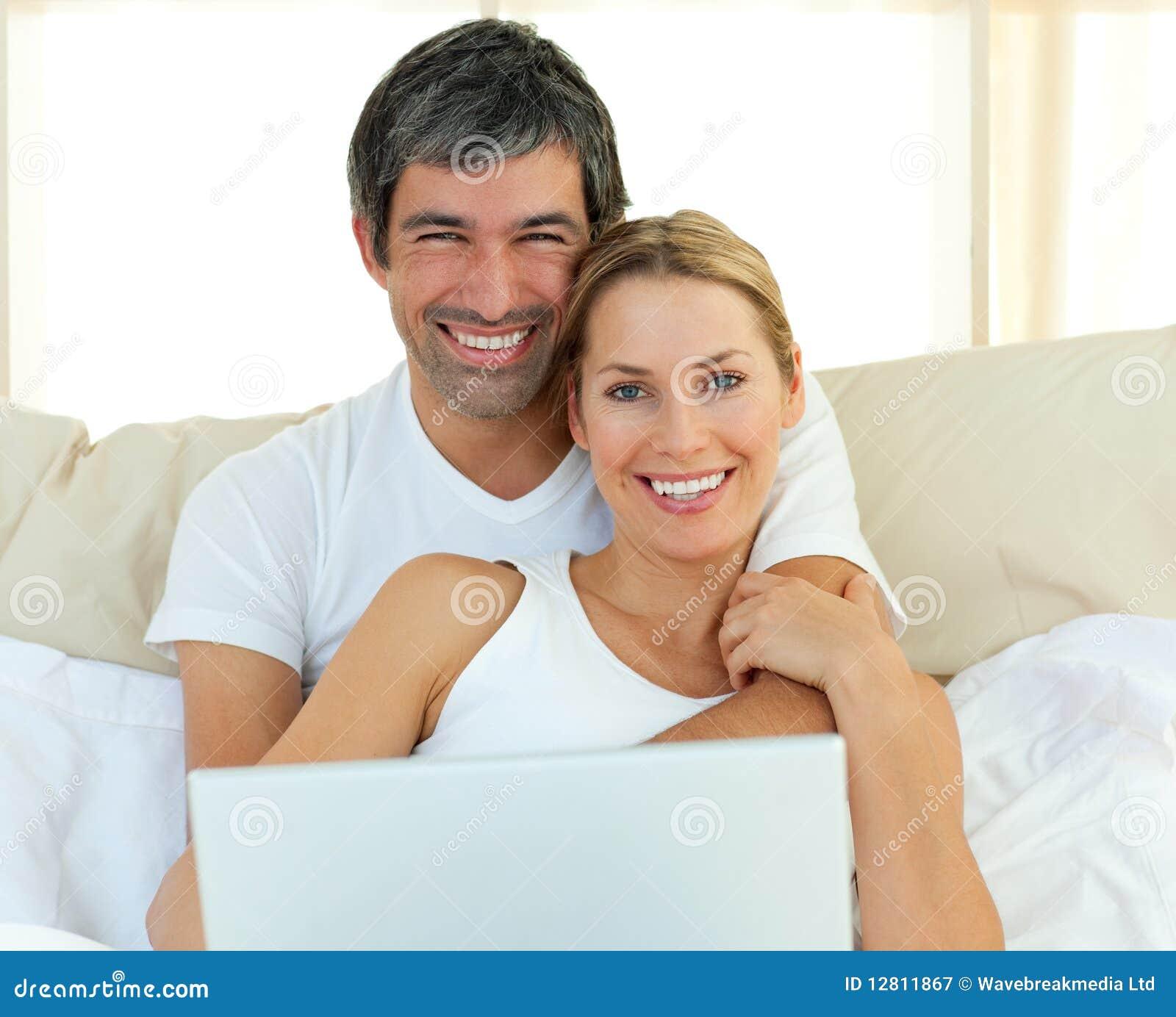 Pares de sorriso usando um portátil que encontra-se na cama