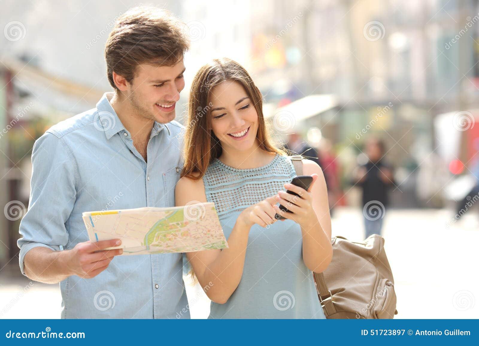 Pares de turistas que consultam gps da cidade de um guia e do smartphone