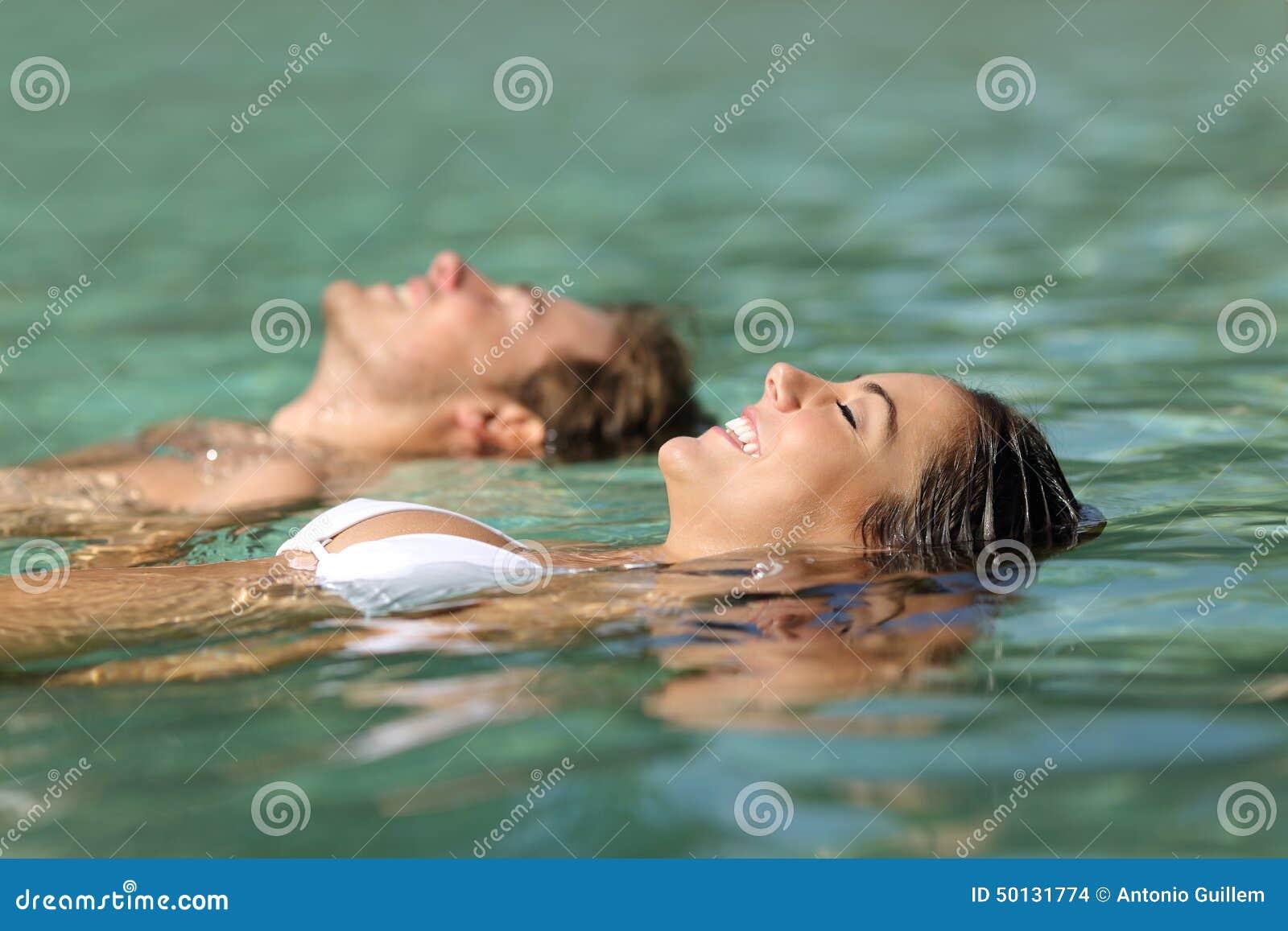 Pares de turistas que nadam no mar de um recurso tropical