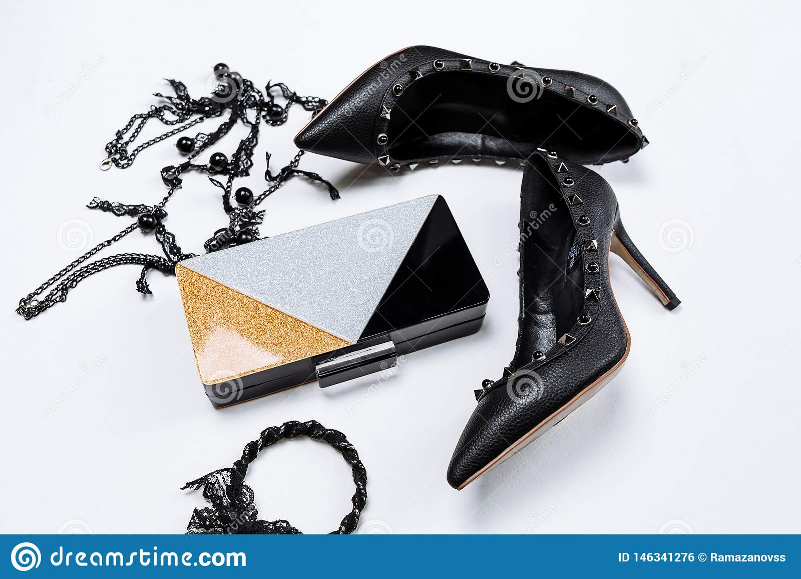 Pares de zapatos negros adornados con acentos del metal, joyer?a con el cord?n y las gotas negros y un embrague tricolor con las