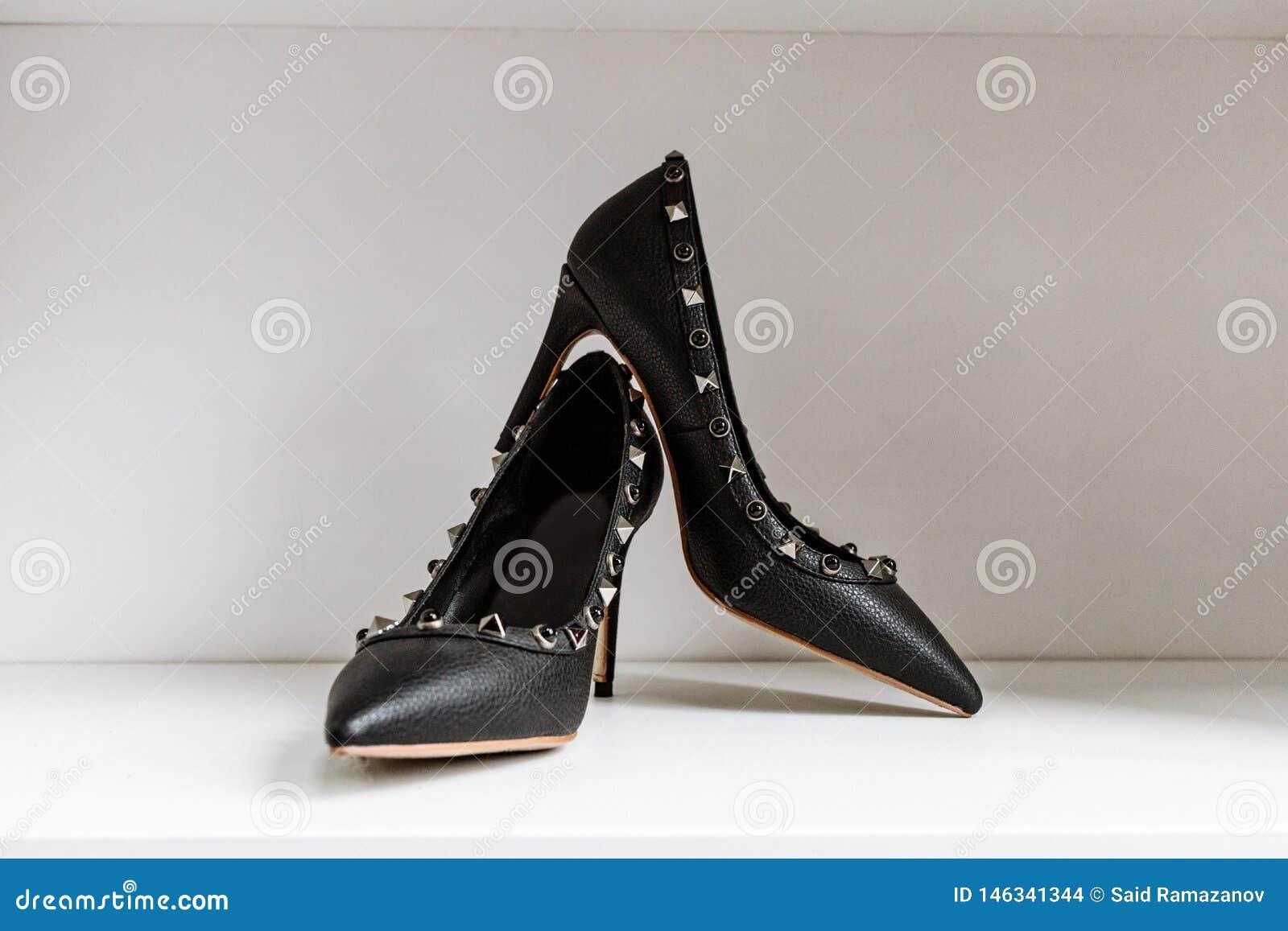 Pares de zapatos de tacón alto negros con las puntas puntiagudas, adornados con los partes movibles del metal contra un estante e