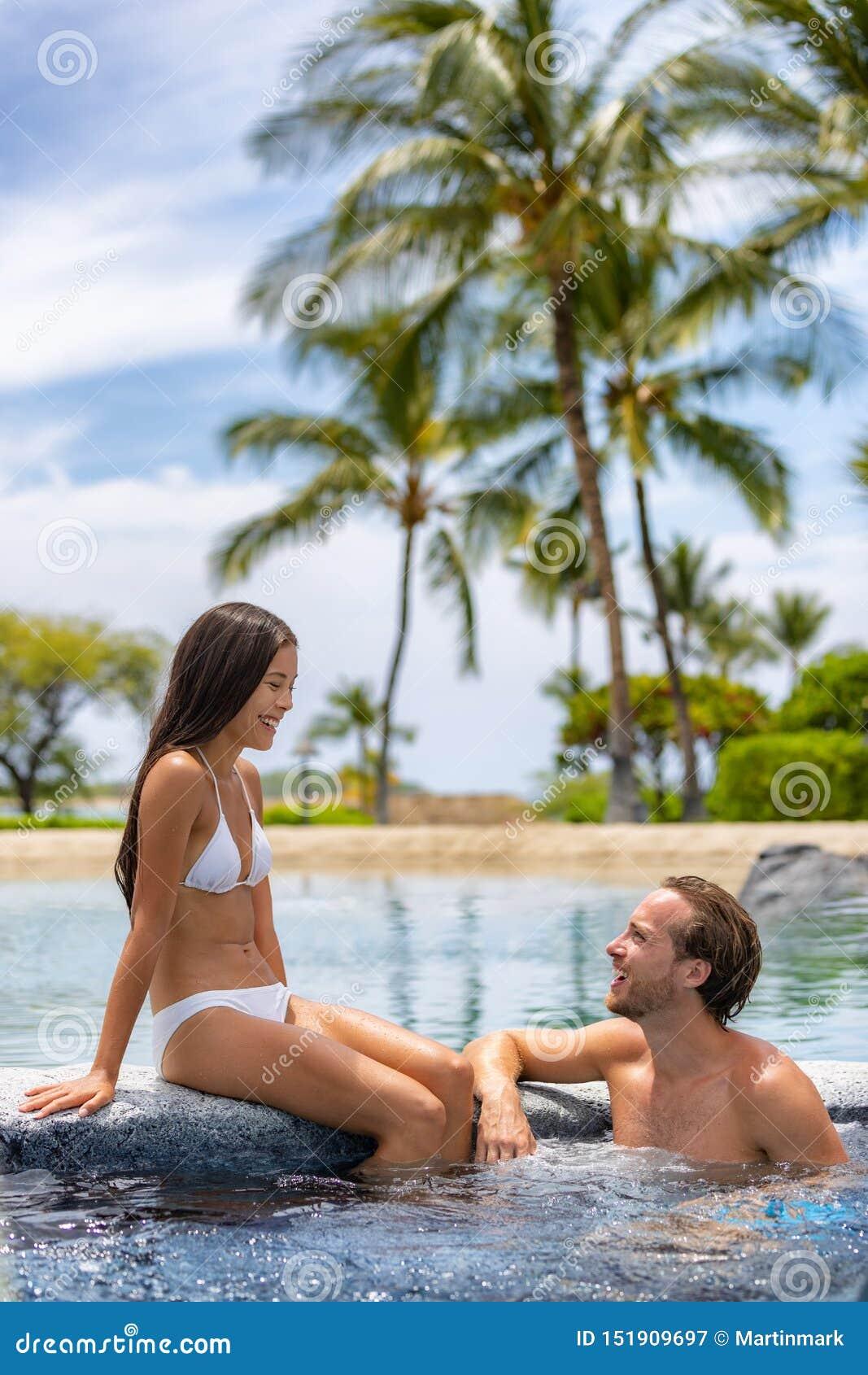 Pares del balneario que se relajan gozando de la piscina de la tina caliente del Jacuzzi al aire libre en partida de la luna de m