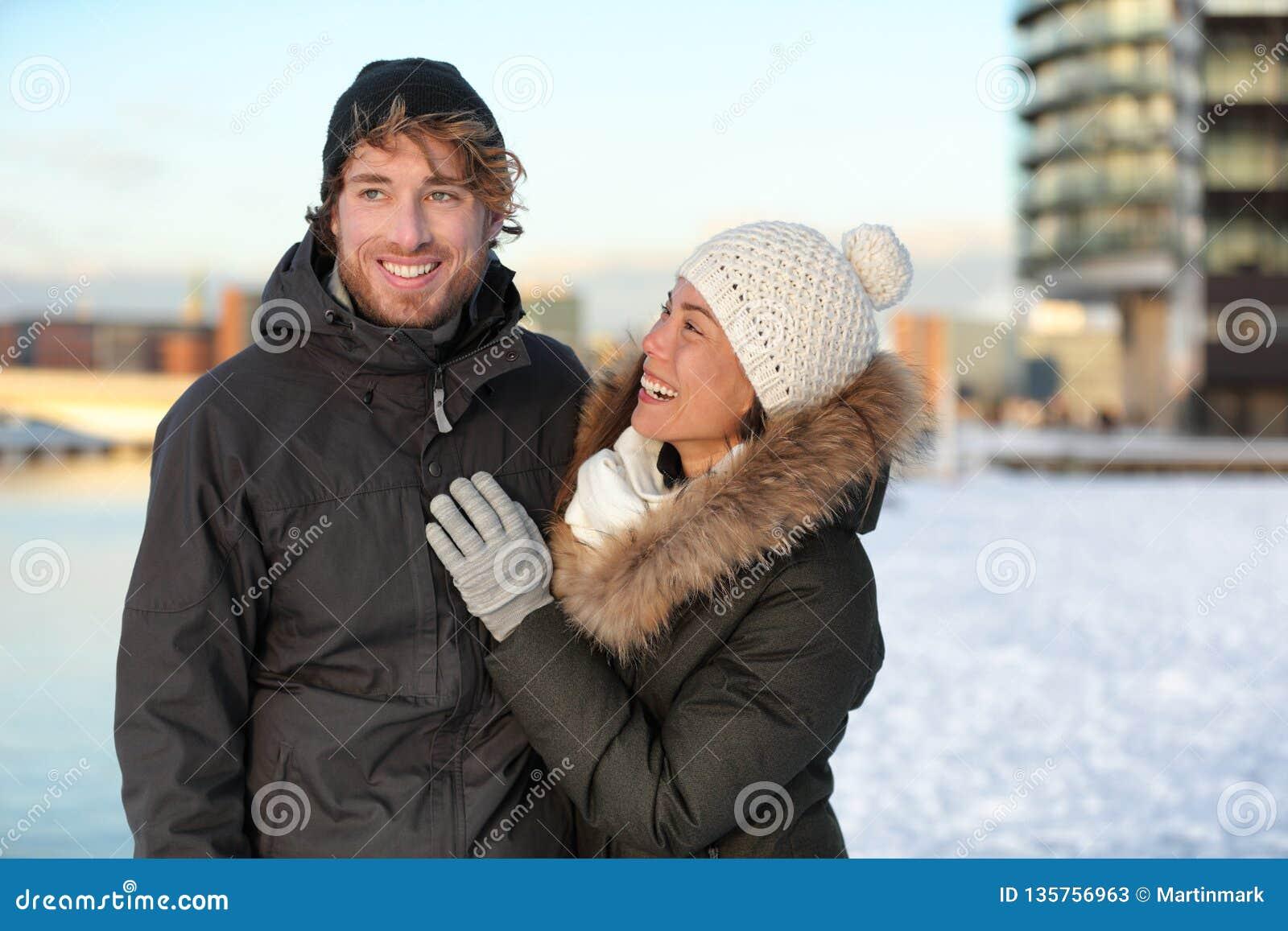 Pares del invierno que caminan en nieve con el sombrero y las capas