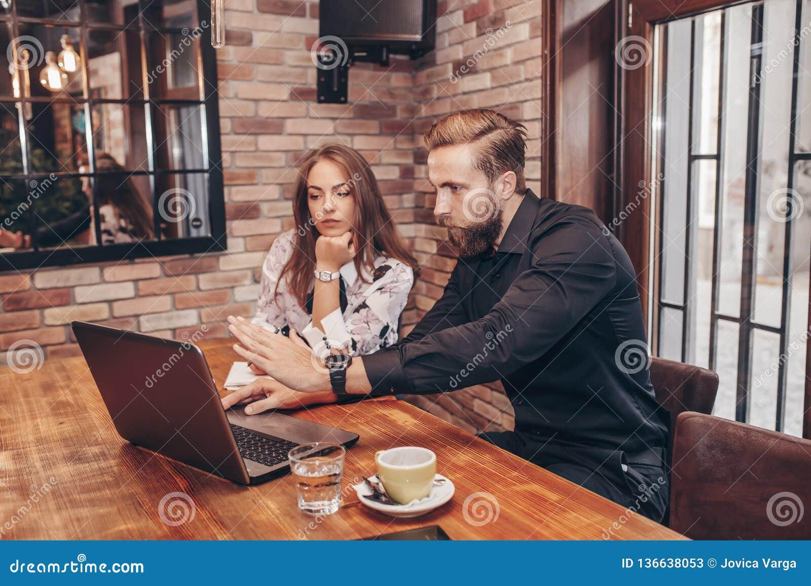 Pares del negocio usando el ordenador portátil y tener una conversación