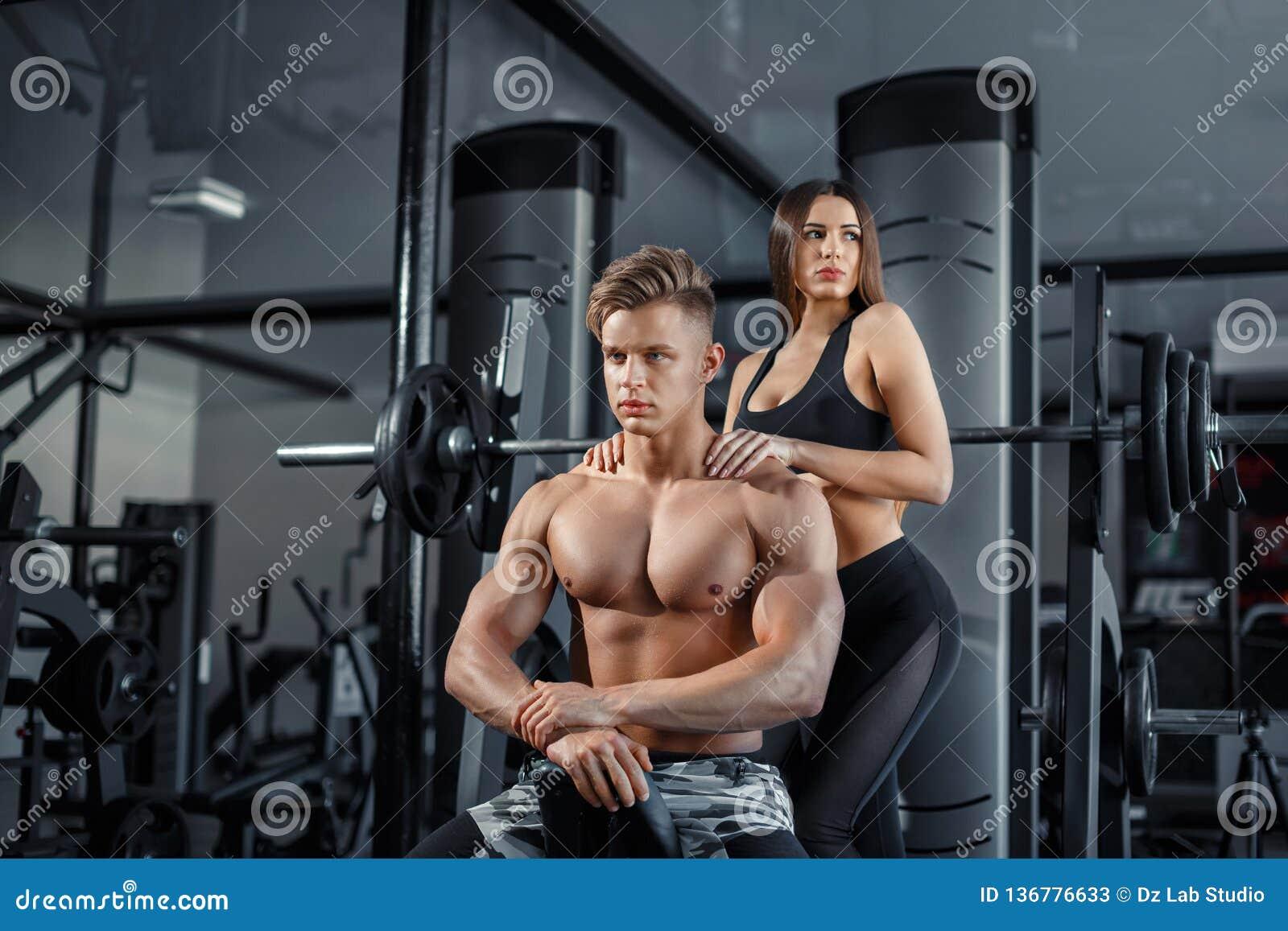 Pares deportivos jovenes hermosos que muestran el músculo y el entrenamiento en gimnasio durante photoshooting