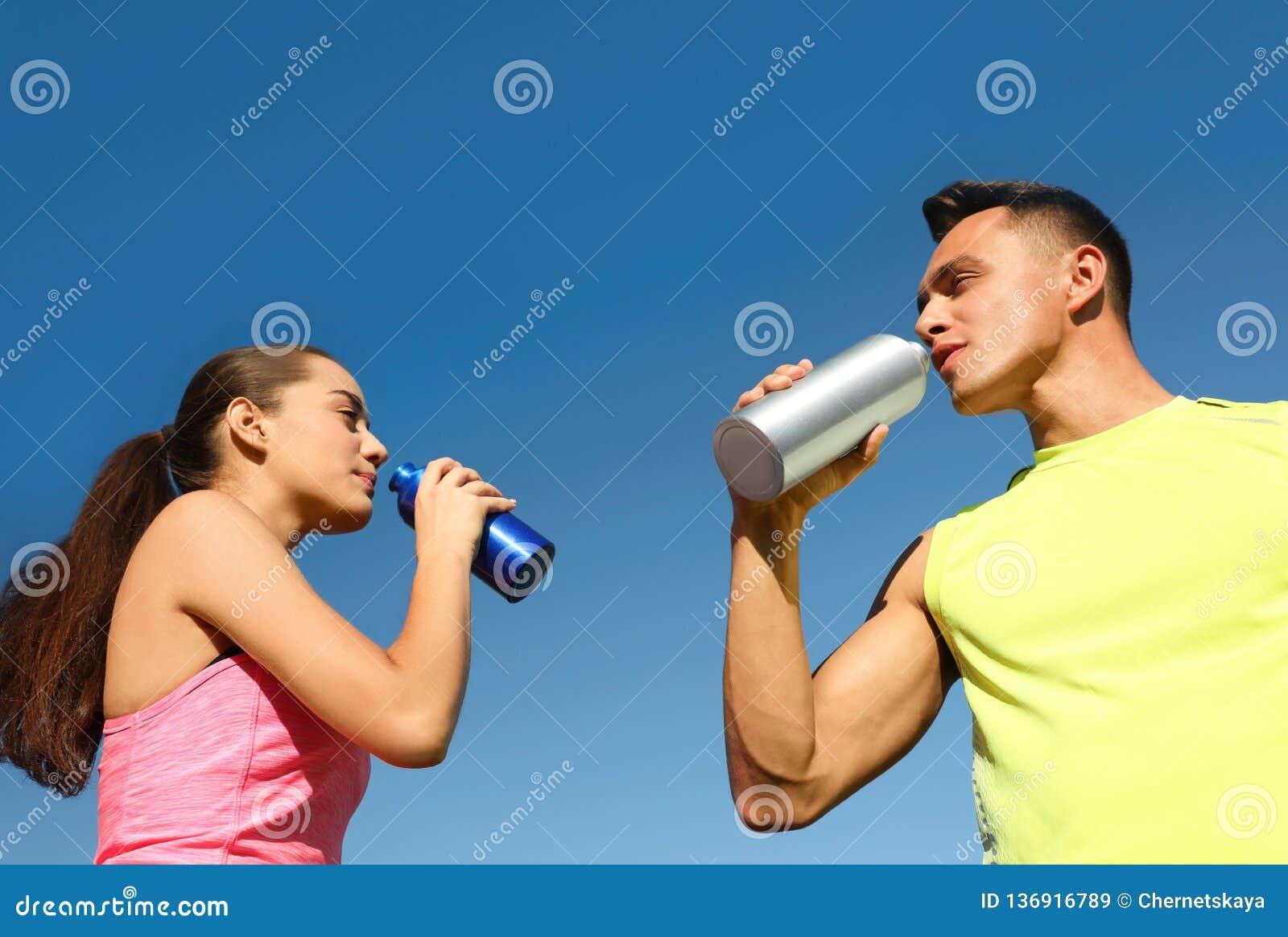 Pares deportivos jovenes que beben de las botellas de agua contra el cielo azul