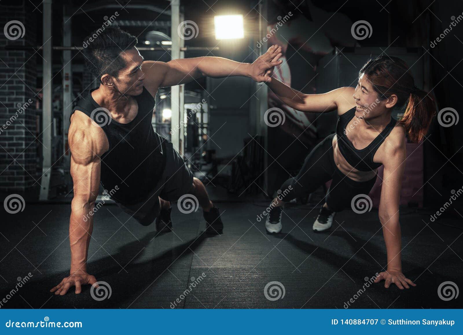Pares desportivos novos que dão certo junto no gym, no homem da aptidão e na mulher dando-se uns cinco altos após a sessão de for