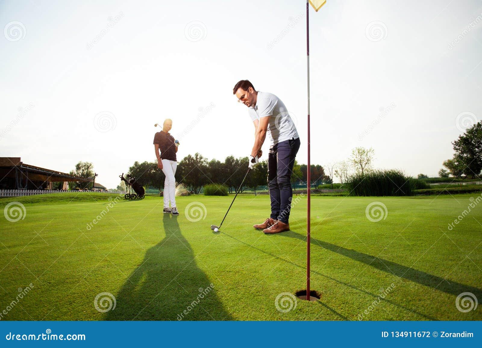 Pares desportivos novos que jogam o golfe em um campo de golfe - imagem