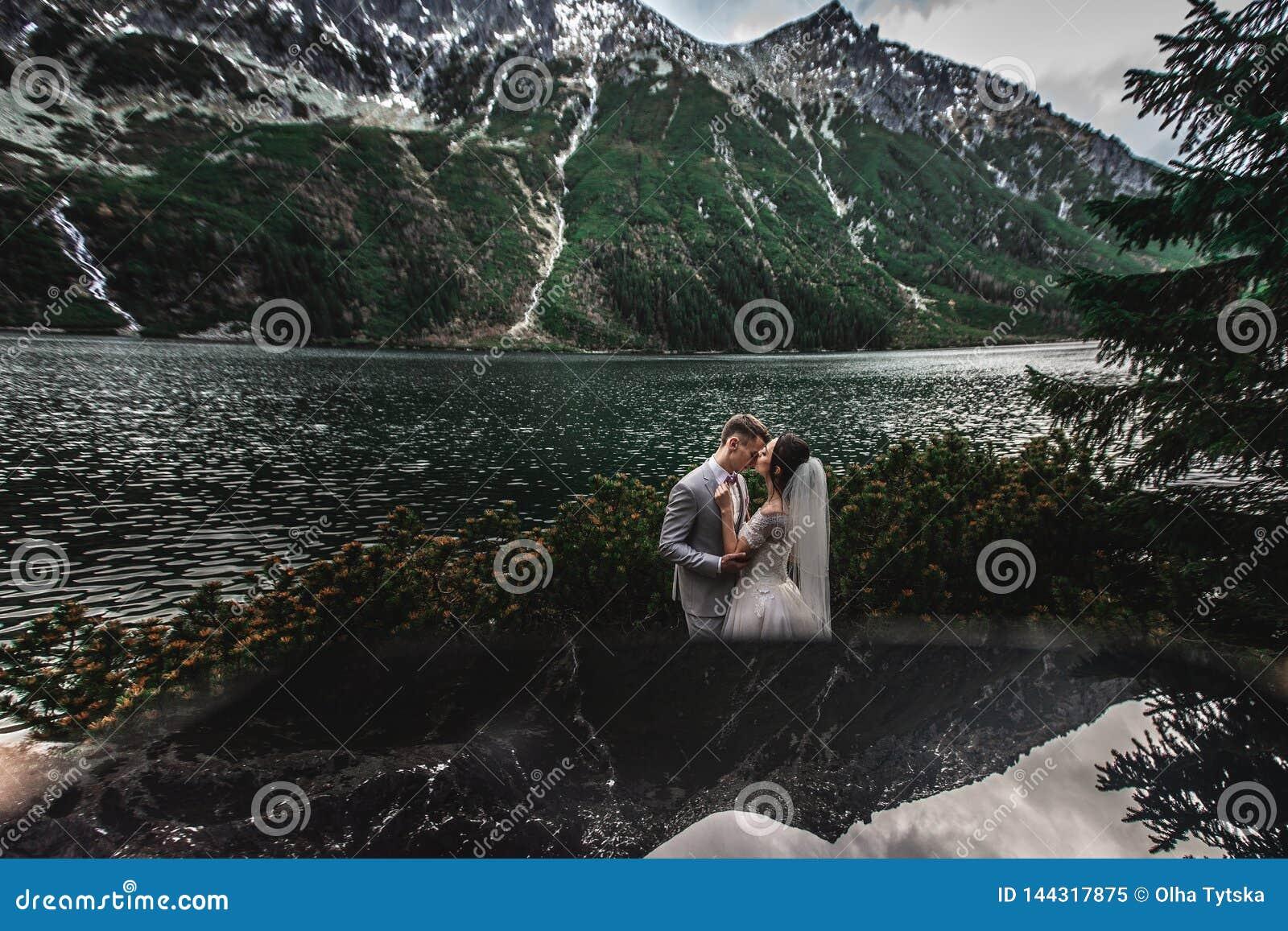 Pares do casamento que beijam perto do lago em montanhas de Tatra no Pol?nia Morskie Oko Dia de ver?o bonito