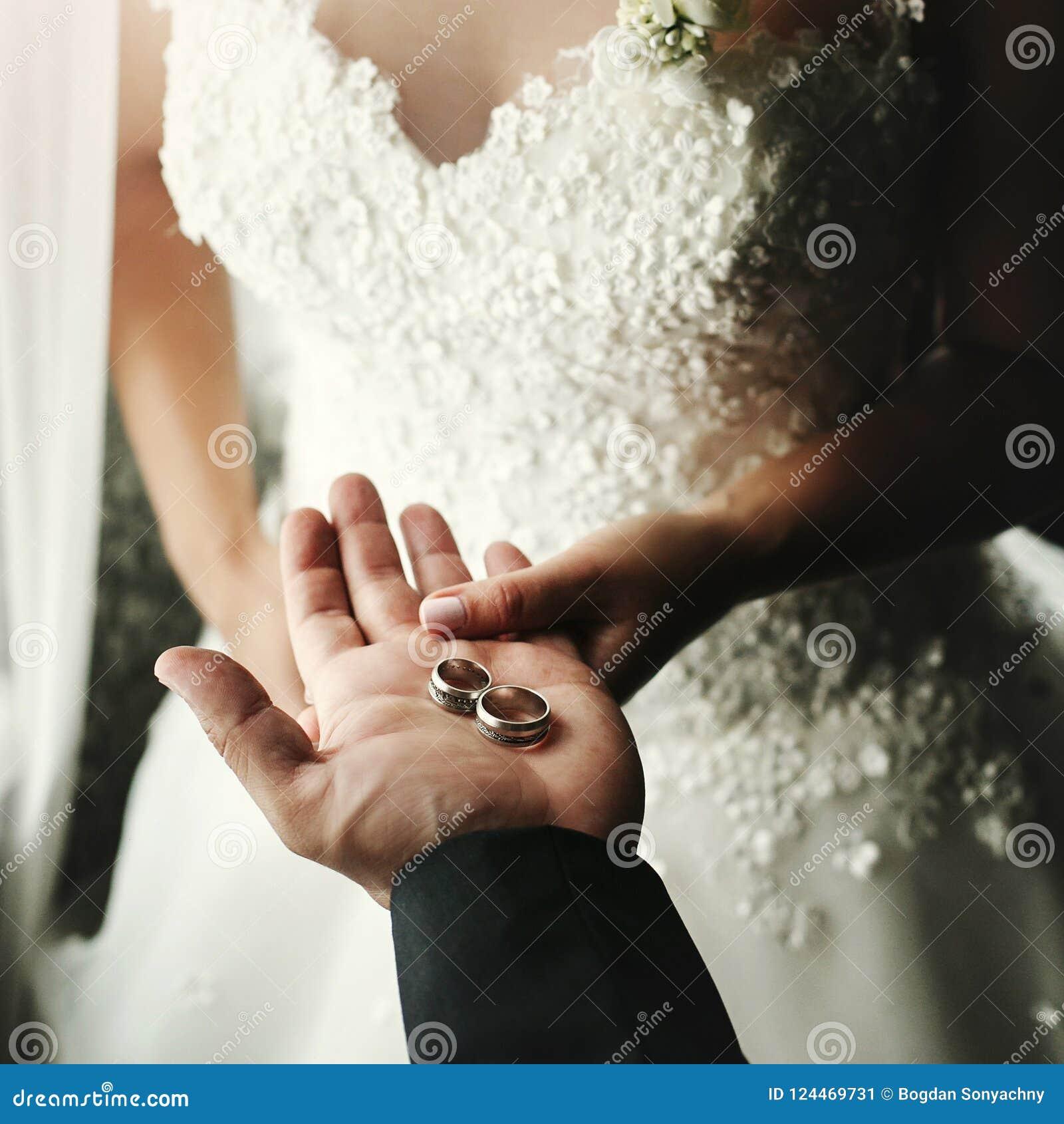 Pares do casamento que guardam as alianças de casamento luxuosas, noivo que mostra a noiva