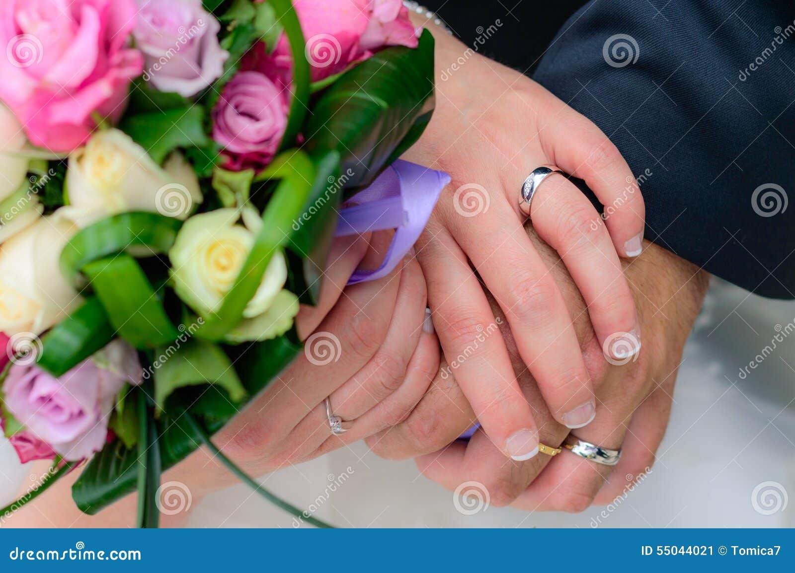 Pares do casamento que guardam as mãos com seus anéis