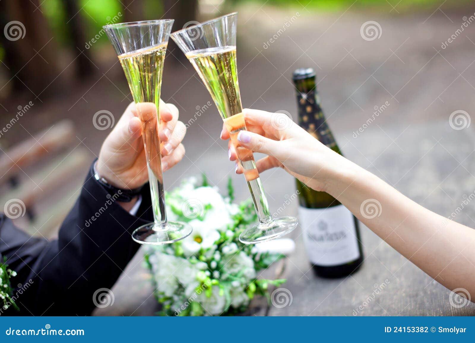 Pares do casamento que mantêm os vidros do champanhe unidos
