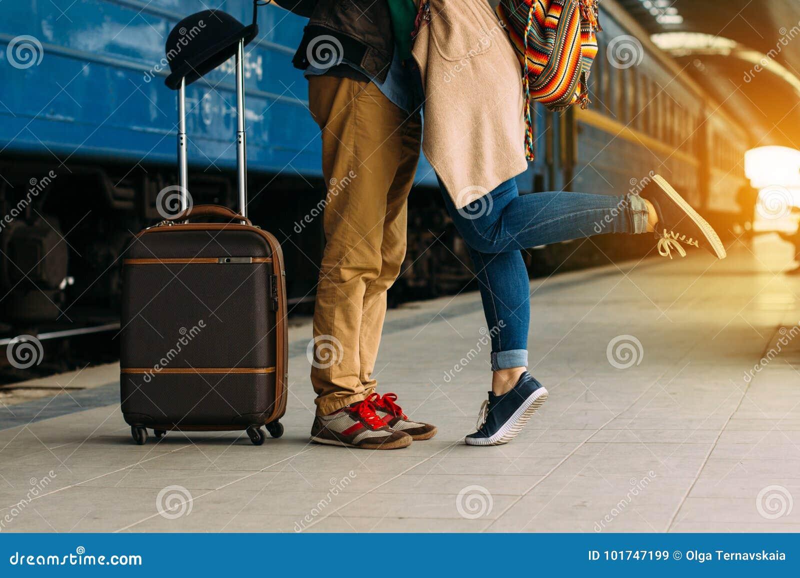Pares do curso de amantes novos que beijam fora com o close up nos pés e nas sapatas Estação de caminhos-de-ferro no fundo Noite