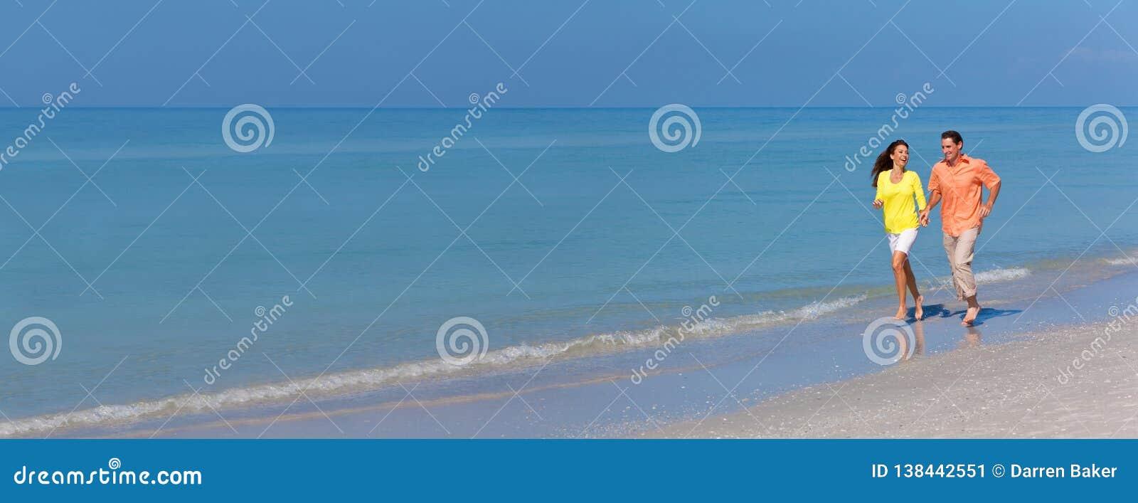 Pares do homem & da mulher do panorama que correm em uma praia