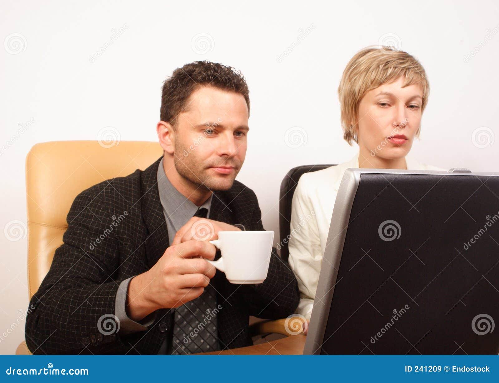 Pares do negócio que trabalham no portátil