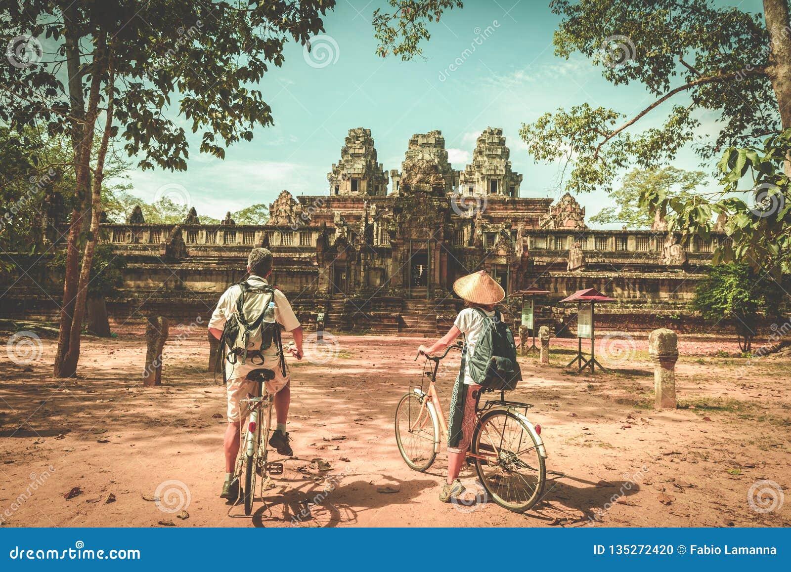 Pares do turista que dão um ciclo em torno do templo de Angkor, Camboja Ruínas da construção de Ta Keo na selva Viagem amigável d
