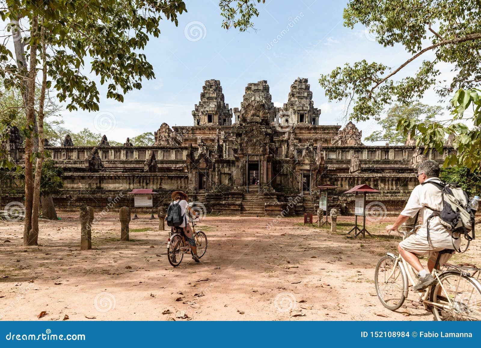 Pares do turista que d?o um ciclo em torno do templo de Angkor, Camboja Ru?nas da constru??o de Ta Keo na selva Viagem amig?vel d