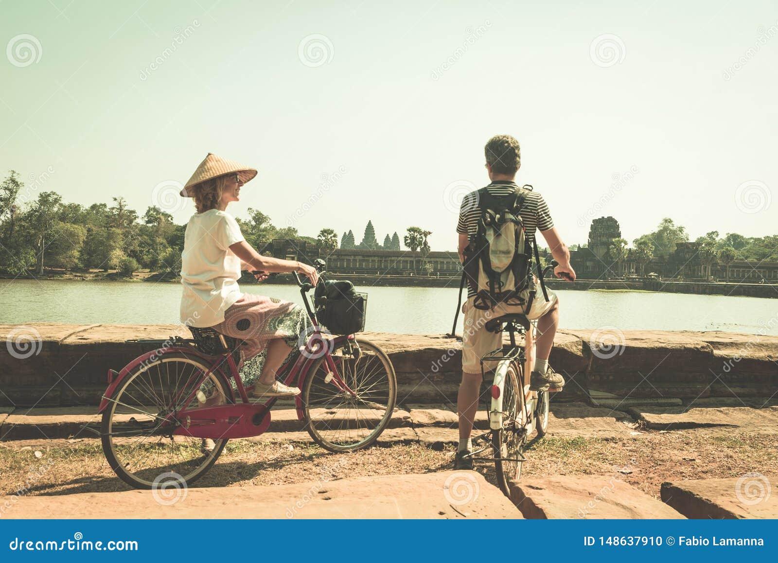 Pares do turista que d?o um ciclo no templo de Angkor, Camboja A fachada principal de Angkor Wat refletiu na lagoa de ?gua Viagem