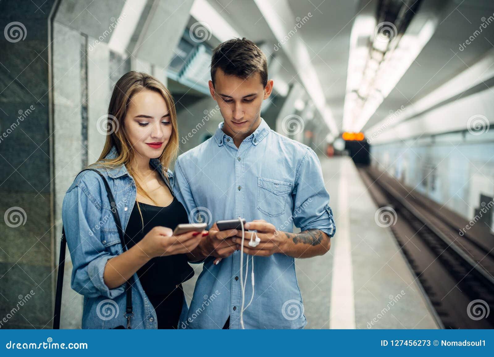 Pares do viciado do telefone usando o dispositivo no metro